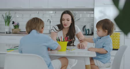 портфель : Two children of boys draw with his mother sitting in the kitchen. Happy family at home. Brothers draw at the table. Real people.