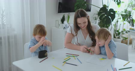 портфель : Mom and her two sons sitting at the kitchen table drawing colored pencils family drawing on the lawn in the summer. Boys learn to draw, and mom helps with drawing Стоковые видеозаписи