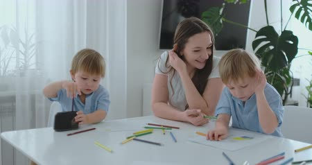 brothers : Mom sitting at the table with two sons Boy sharpening a colored pencil in a sharpener sitting at the kitchen table. The second boy draws a picture with pencils Stock Footage