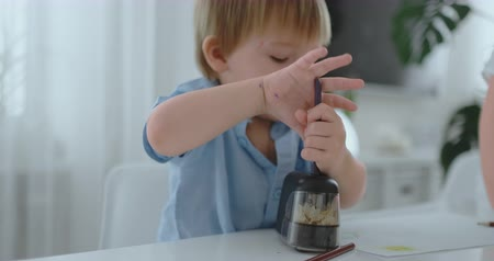 puntenslijper : Boy sharpening a colored pencil in a sharpener sitting at the kitchen table