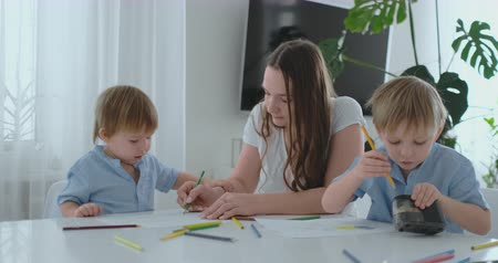brothers : Young Mom and two sons 2-4 years old draw pencils drawing on boomega sitting at the living room table in slow motion Stock Footage