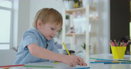 elementary age : Smiling boy in blue shirt draws on paper with a pencil while sitting at the table in the living room Stock Footage