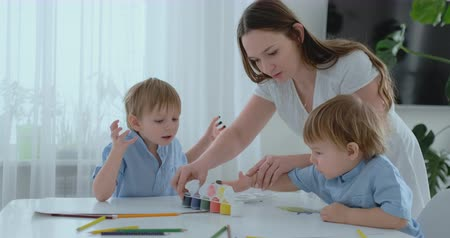 kitchen paper : Mom helps her sons to develop creative skills and is engaged with them to create drawing paints with the help of fingers. Child development. Creative family. Loving mom