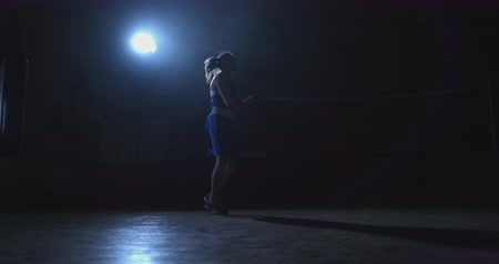 сильный : Young beautiful woman boxer in training in the hall jumping rope