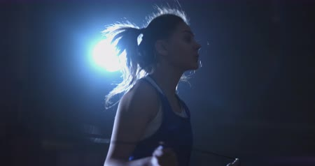 senza volto : Young beautiful woman boxer in training in the hall jumping rope close-up