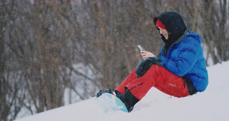 starszy pan : A male snowboarder sitting on the snow takes photos on the phone of a beautiful resort landscape for social networks. Resort blogger