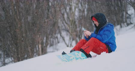 snowboarden : A male snowboarder sitting on the snow takes photos on the phone of a beautiful resort landscape for social networks. Blogger at the resort. Write text messages to friends using your smartphone Stockvideo