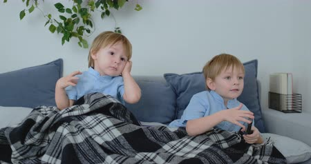 yorgan : Two boys, 4 and 2 years old, are watching TV sitting on the couch. An exciting TV show. View cartoons