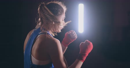 épuisement : Female boxer training in dark room with back light in slow motion. steadicam shot Vidéos Libres De Droits