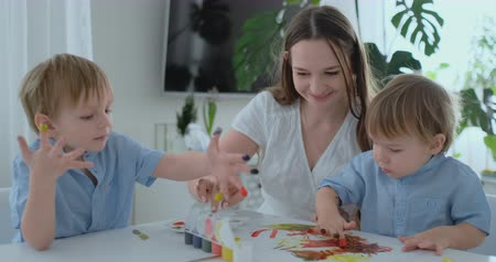 kitchen paper : The family has fun painting on paper with their fingers in paint. Mom and two children paint with fingers on paper Stock Footage