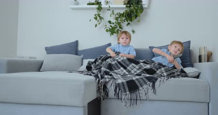 мультфильмы : Two boys, 4 and 2 years old, are watching TV sitting on the couch. An exciting TV show. View cartoons