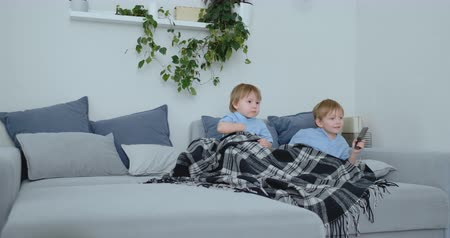 family watching tv : Two children watch an exciting TV show on TV. Two brothers are watching TV Stock Footage