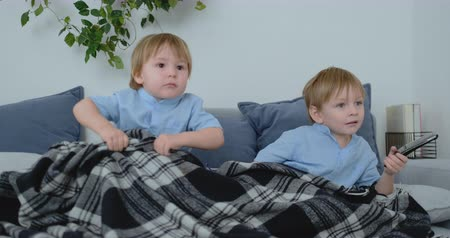 yorgan : Two children watch an exciting TV show on TV. Two brothers are watching TV Stok Video