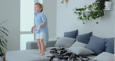 wandklok : Two little boys jumping on the couch and having fun. Joy, laughter and fun at home Stockvideo