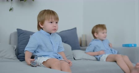 paplan : Two boys, 4 and 2 years old, are watching TV sitting on the couch. An exciting TV show. View cartoons