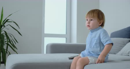 fratellanza : A 2 years old boy sits on a sofa and watches TV sitting with a remote control in his hands. Filmati Stock