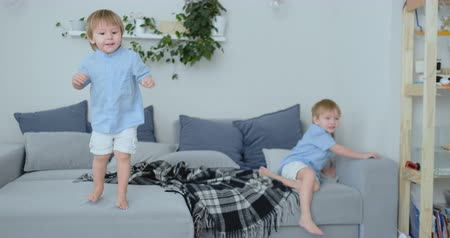 yorgan : Two little boys jumping on the couch and having fun