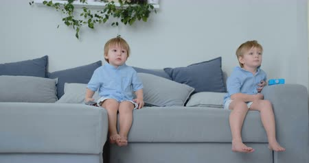 karikatury : The kids are watching tv. Small children sitting on the couch watching cartoons