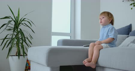 yorgan : A 2 years old boy sits on a sofa and watches TV sitting with a remote control in his hands. Stok Video