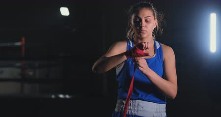 desafio : Woman is wrapping hands with yellow boxing wraps. Self Defense for Women. Isolated on black with red nails. Strong hand and fist, ready for fight and active exercise