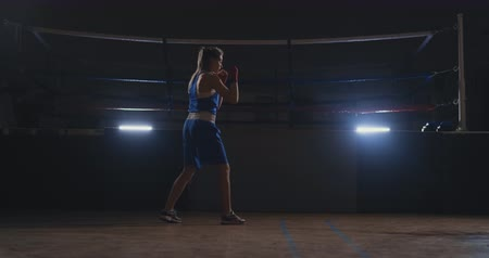 tekmeleme : A beautiful woman conducts a shadow fight while practicing hard for future victories. Dark gym background. steadicam shot Stok Video