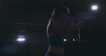 diferansiyel odak : Professional beautiful female boxer otbryvatyvat blows conducting a fight with a shadow in a dark hall of the hall in slow motion in blue clothes and red bandages on her wrists. flying around the object. steadicam shot
