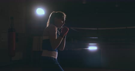 diferansiyel odak : steadicam shot Professional beautiful female boxer unloads strikes while conducting a shadow fight in a dark hall room in slow motion in a blue dress and red bandages on her wrists. flying around the object