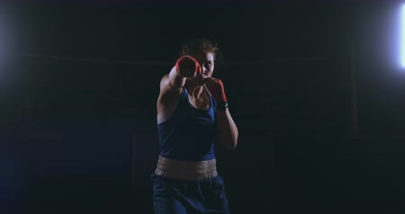 ラッピング : Looking into the camera a beautiful female boxer strikes against a dark background with a backlit light. Steadicam shot