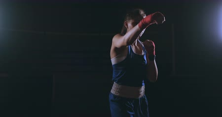 ラッピング : Beautiful sexy woman boxer dynamically strikes directly into the camera and moving forward on a dark background with a backlight. Camera moves Steadicam shot 動画素材