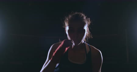 bandagem : Beautiful sexy woman boxer dynamically strikes directly into the camera and moving forward on a dark background with a backlight. Steadicam shot