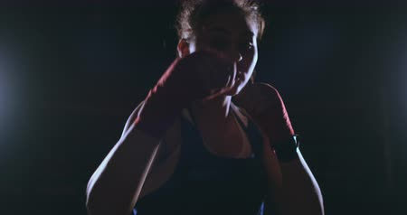 стремление : Looking into the camera a beautiful female boxer strikes against a dark background with a backlit light. Steadicam shot