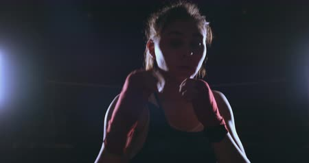 oposto : Beautiful sexy woman boxer dynamically strikes directly into the camera and moving forward on a dark background with a backlight. Steadicam shot