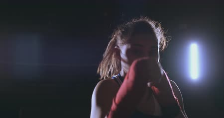 oposto : Beautiful sexy woman boxer dynamically strikes directly into the camera and moving forward on a dark background with a backlight. Camera moves Steadicam shot Stock Footage