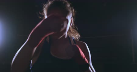 Beautiful sexy woman boxer dynamically strikes directly into the camera and moving forward on a dark background with a backlight. Steadicam shot