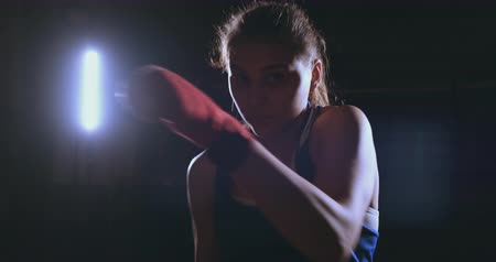 opposite : A beautiful female boxer strikes directly into the camera looking into the camera and moving forward on a dark background with a backlight. Steadicam shot Stock Footage
