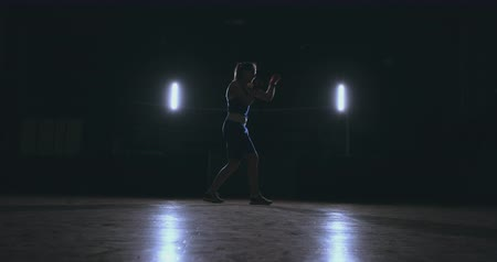 harcoló : A beautiful woman boxer trains in a dark gym and works out punches in slow motion. side view. Steadicam shot
