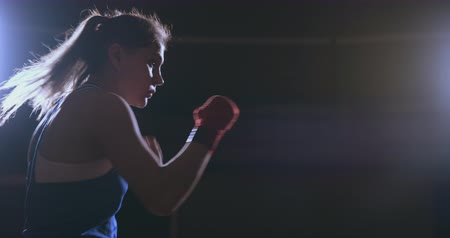 ctižádost : Training a beautiful female boxer doing punches in a dark room. Steadicam shot. Preparation for self-defense and fight in the ring
