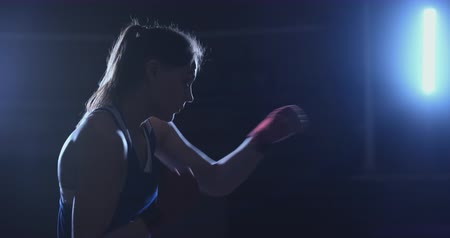 oposto : A beautiful woman boxer trains in a dark gym and works out punches in slow motion. side view. Steadicam shot