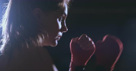 opposite : A beautiful woman boxer trains in a dark gym and works out punches in slow motion Stock Footage
