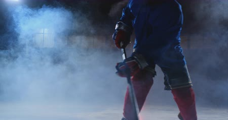 western script : Professional hockey player with a stick and a puck moves on Luda in skates and helmet on a dark background and smoke. Dribbling with the puck of a young man on the ice arena