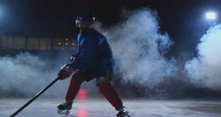 western script : Professional hockey player with a stick accelerates on the ice and stops abruptly in front of the camera looking straight into the camera