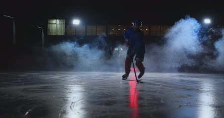 western script : Male hockey player with a puck on the ice arena shows dribbling moving directly into the camera and looking directly into the camera against a dark background in the smoke Stock Footage