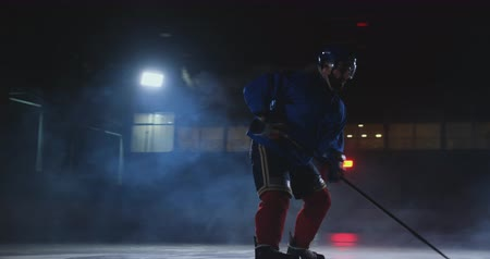 western script : Man hockey player with a puck on the ice in hockey form leaves with a stick in his hands out of the darkness and looks straight into the camera Stock Footage