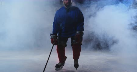 western script : Man hockey player with a puck on the ice arena shows dribbling moving directly to the camera and looking straight into the camera Stock Footage