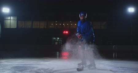 western script : Man hockey player in hockey uniform leaves with a stick in his hands out of the darkness and looks straight into the camera Stock Footage
