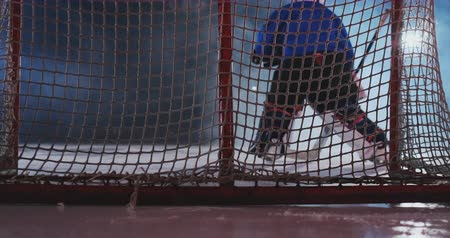 western script : Hockey player carries out an attack on the opponents goal and scores a goal puck beating the goalkeeper. Visas for the hockey goal. Rear view Stock Footage