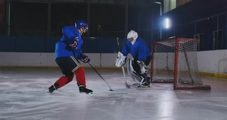 вратарь : Professional hockey player attacks the gate and strikes, but the goalkeeper beats the puck. A goal in hockey. Puck scored