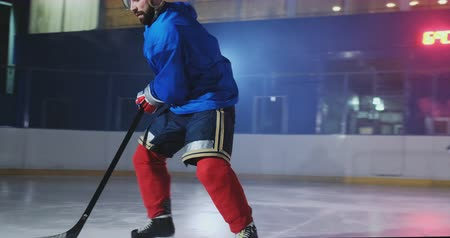 temperatura : Hockey forward carrying a puck, skating past an opposing defenseman and taking a slap shot goaltender preventing the scoring of a goal by catching the puck