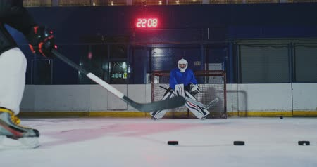 western script : Close-up of a hockey puck in slow motion and a putter of several pucks in turn and a goalkeeper in the background
