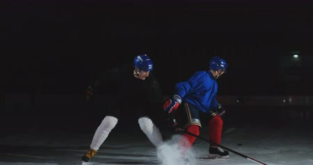 western script : 2 hockey players fighting for puck, legs, skates close view Stock Footage
